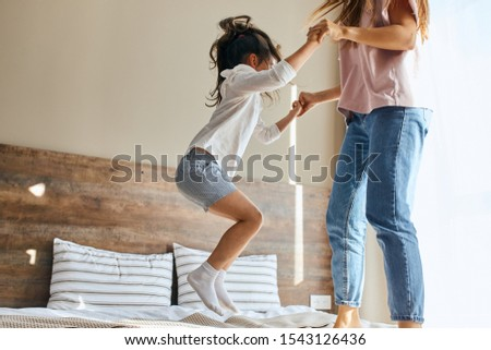 Portrait of little joyful six years old girl happily jumping on bed together with sister in brightly lighted bedroom, shot from below, family joy concept