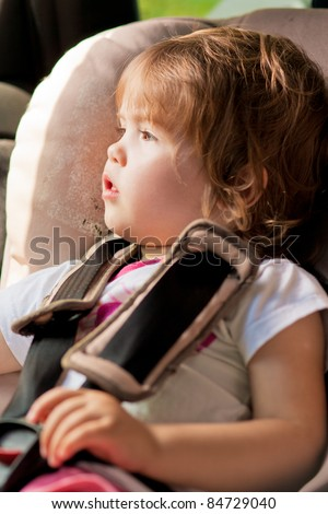 portrait of little kid in safety seat looking through window pan