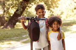 Portrait of little kids.  African American brother and sister in nature with e-scooter.