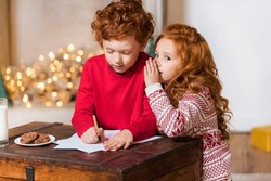 portrait of little kids writing wish list for santa together at home