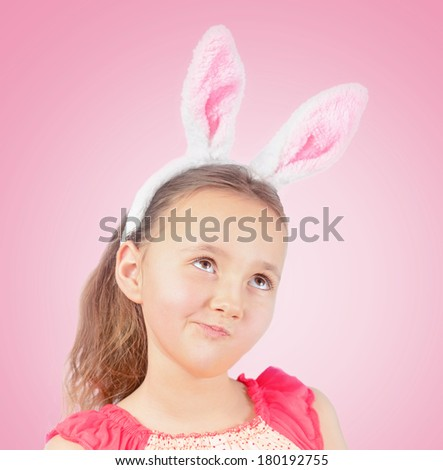 Portrait of little pensive girl dressed in Easter bunny ears on a pink background