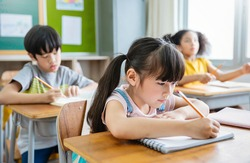 Portrait of little pupil writing at desk in classroom at the elementary school. Student girl doing test in primary school. Children writing notes in classroom. Education knowledge concept