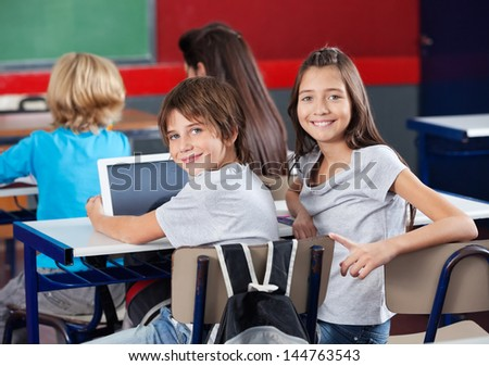 Portrait of little schoolchildren with digital tablet sitting at desk in classroom - stock photo