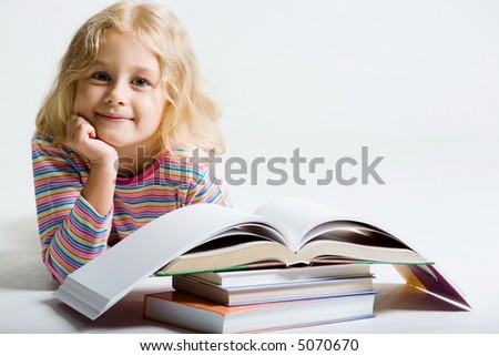 Portrait of little schoolgirl smiling from behind books on a white background
