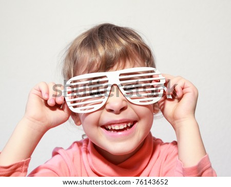 Portrait of little smiling girl she try on white glasses-shutters