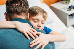 portrait of little son hugging father in hospital chamber