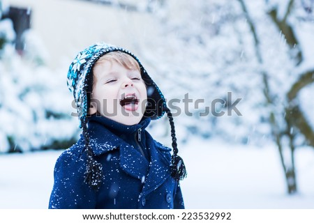 Portrait of Little toddler boy in winter clothes with falling snow