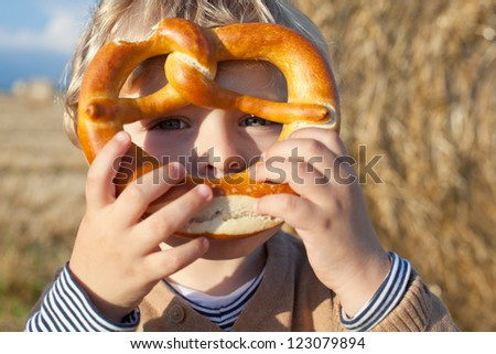 Portrait of little toddler boy looking through fresh baked pretzel outdoors