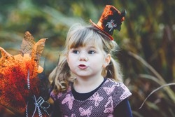 Portrait of little toddler girl dressed as a witch celebrates Halloween. Happy child outdoors, with orange funny hat and hold witch broom. Beautiful family festival season in october. Outdoor activity