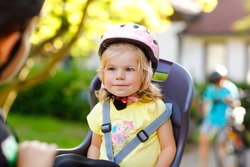 Portrait of little toddler girl with security helmet on the head sitting in bike seat of parents. Boy on bicycle on background. Safe and child protection concept. Family and weekend activity trip.