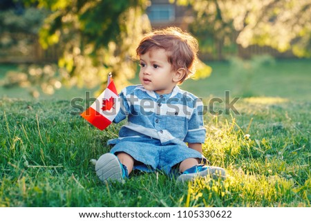 portrait of little white Caucasian baby boy holding Canadian flag with red maple leaf. Toddler celebrating national Canada day sitting on grass in summer  park outside