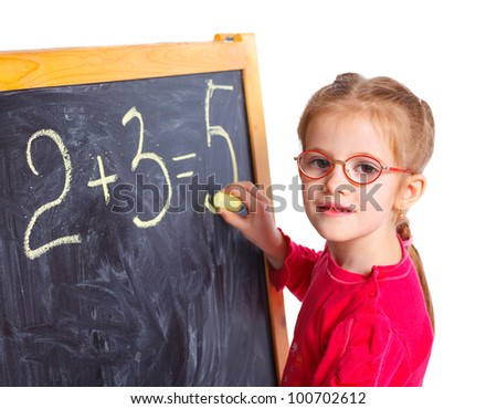 Portrait of llittle girl in the glasses is drawing on a blackboard. Isolated on white background