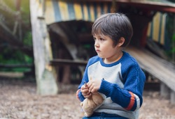 Portrait of Lonely kid holding doggy toy sitting alone in the playground, Sad child sitting with his toy with and looking out with thinking face, little boy playing alone with unhappy face.