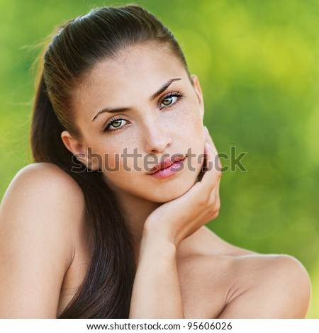portrait of long-haired, beautiful, naked women standing shoulder lifting background summer green park