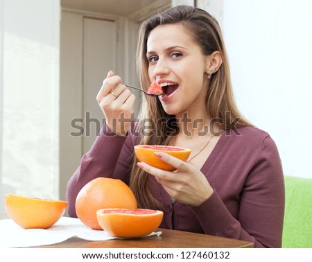 Portrait of long-haired girl eating grapefruit at home