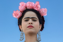 Portrait of look alike popular Mexican artist Frida Kahlo with her fashion statement with bright red floral head piece,  ornament and popular Unibrow over a blue background.
