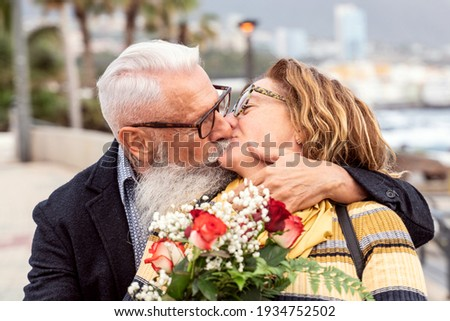 Portrait of lovely attractive cheerful couple of seniors hugging and kissing during the anniversary date. Handsome man surprised his wife with flowers on valentine's day. Real people emotions. Foto stock ©