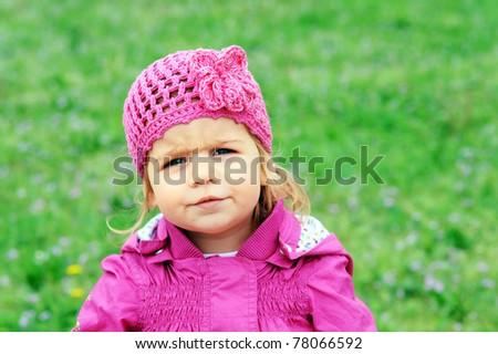 Portrait of lovely baby girl against green filed background