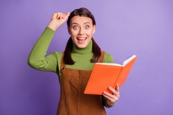 Portrait of lovely brainy amazed cheerful girl reading interesting book having fun isolated over bright violet color background