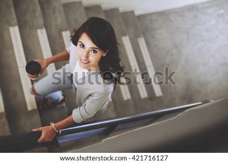 Portrait of lovely brunette walking up the stair, view from above #421716127