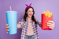 Portrait of lovely cheerful girl giving you soda tasty yummy french fries winking isolated over bright violet purple color background