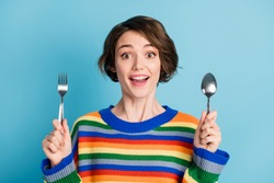 Portrait of lovely cheerful girl holding fork spoon waiting domestic tasty delicious dinner isolated over bright blue color background