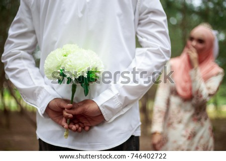 Portrait of lovely couple, a man hiding flowers, making surprise. Blurred woman smiling and surprising. Selective focus. Nature background. Marriage proposal, engagement, and love concept. #746402722