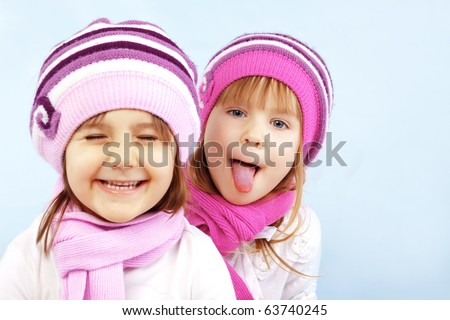 Portrait of lovely embracing kid girls wearing winter clothing