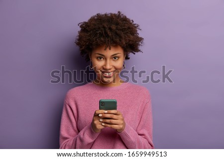 Portrait of lovely ethnic woman holds modern mobile phone, uses electronic device on surfing web, looks positively at camera, connected to wireless internet, wears casual sweater, poses indoor