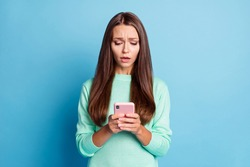 Portrait of lovely focused sullen brown-haired girl using gadget browsing bad news media isolated over bright blue color background