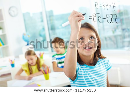 Portrait of lovely girl doing sums on transparent board with two schoolmates on background