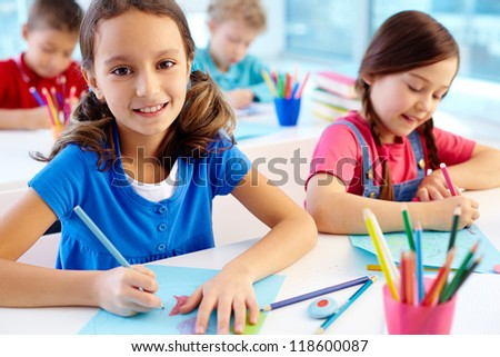 Portrait of lovely girl drawing at workplace and looking at camera with schoolmates on background