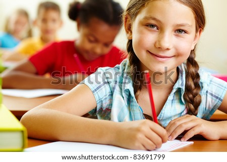 Portrait of lovely girl drawing in copybook and looking at camera - stock photo