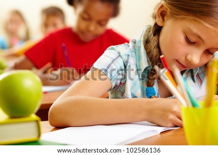 Portrait of lovely girl drawing in copybook at lesson