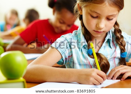 Portrait of lovely girl drawing in copybook at lesson - stock photo