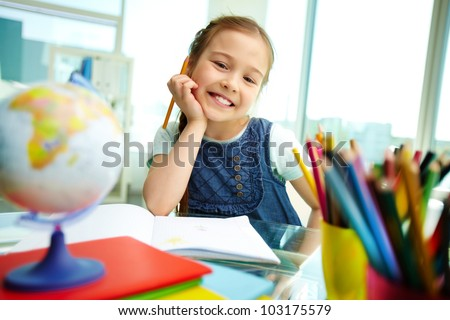Portrait of lovely girl looking at camera while drawing