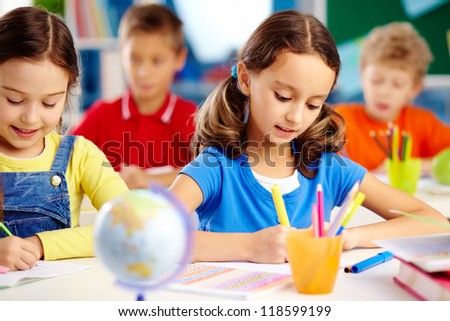 Portrait of lovely girls drawing at workplace with schoolboys on background - stock photo