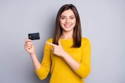 Portrait of lovely glad cheerful girl holding in hands demonstrating bank card solution isolated over grey color background
