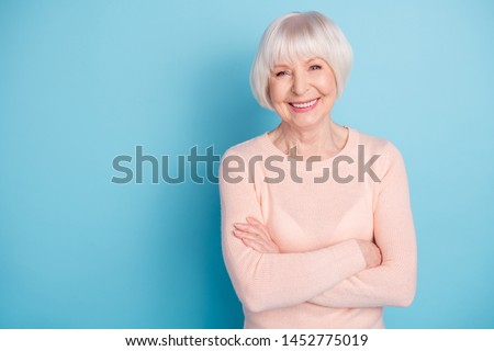 Portrait of lovely lady with her arms folded having toothy smile wearing pastel sweater isolated over blue background