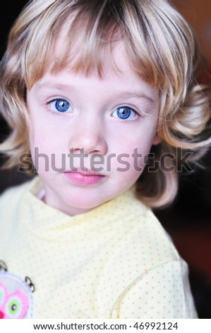 Portrait of lovely little blonde girl with blue eyes