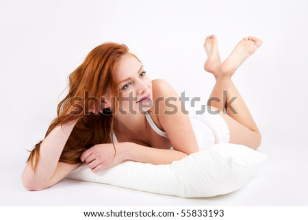 Portrait of lovely redheaded woman with pillow on white