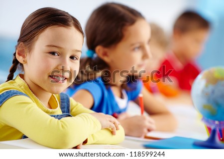 Portrait of lovely schoolgirl at workplace looking at camera with her classmates behind