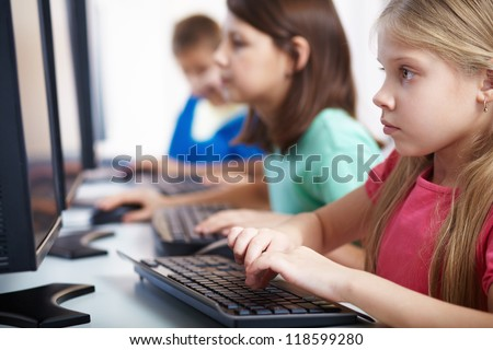 Portrait of lovely schoolgirl looking at computer monitor while typing