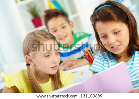 Portrait of lovely schoolgirls reading with schoolmate on background