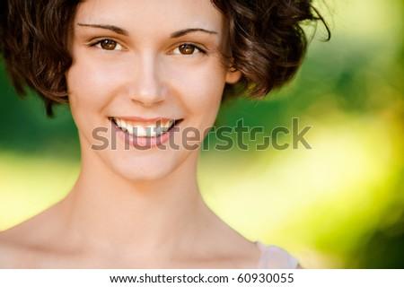 Portrait of lovely smiling girl, on green background.