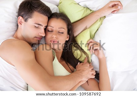 Portrait of lovely young couple sleeping together on bed