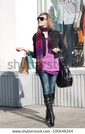 Portrait of lovely young woman smiling and carrying shopping bag