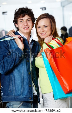 Portrait of loving couple after buying gifts looking at camera with smiles