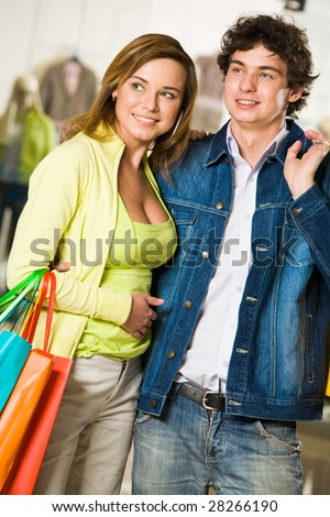 Portrait of loving couple choosing something in trade center and smiling