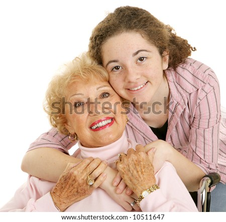 Portrait of loving grandmother and affectionate teen granddaughter.  White background.